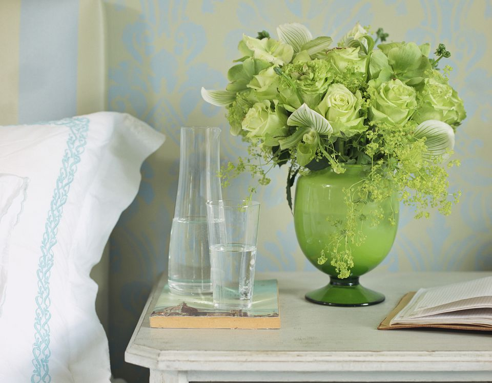 green flowers in a vase on a nightstand