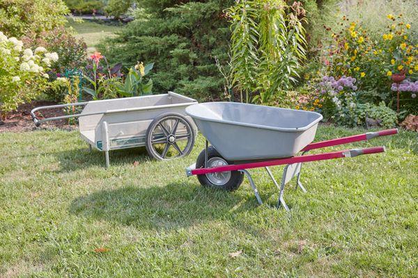 Gray wheelbarrow and garden cart on lawn next to flower garden