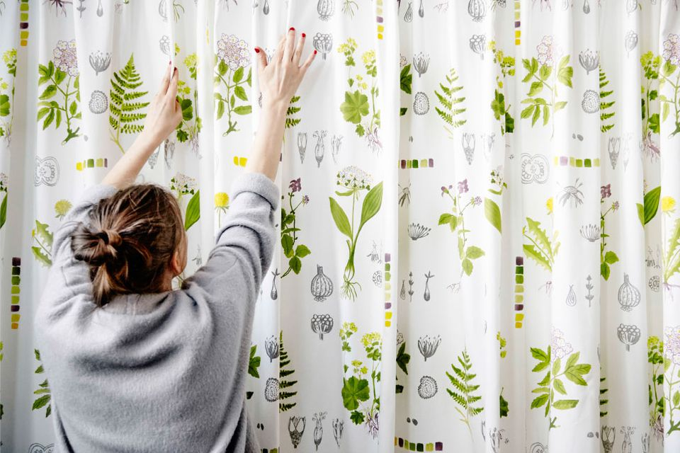 Woman covering a wall with a curtain