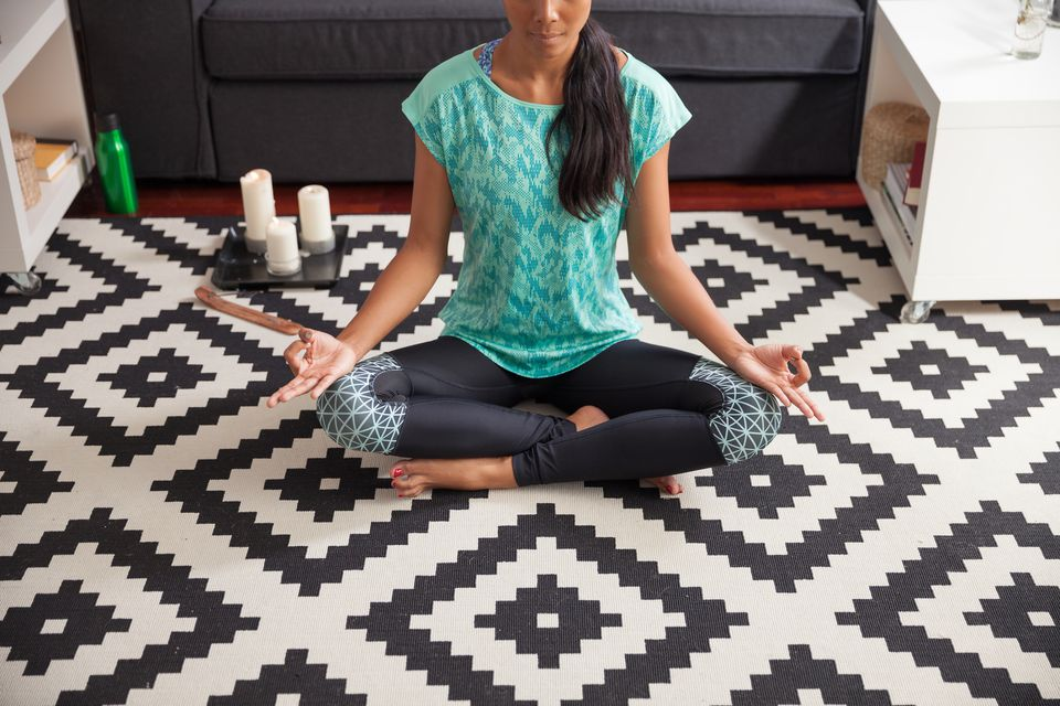 Woman doing yoga on geometric black and white floor tiles
