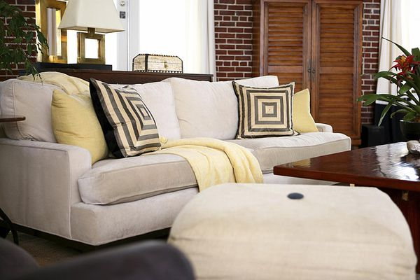 A studio apartment with an off-white sofa and ottoman with brown and yellow pillows and a yellow throw.