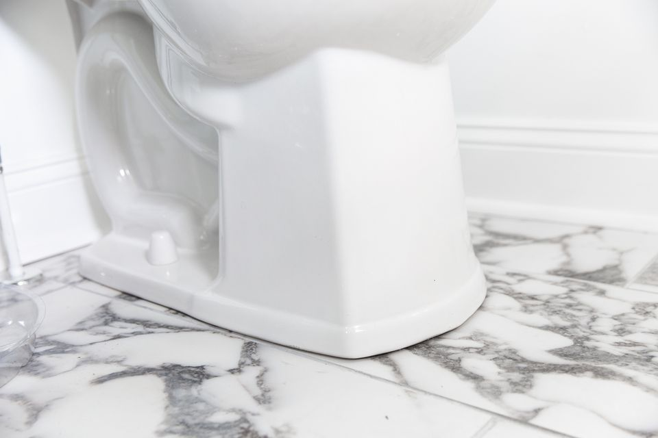 closeup showing the base of a toilet to reset