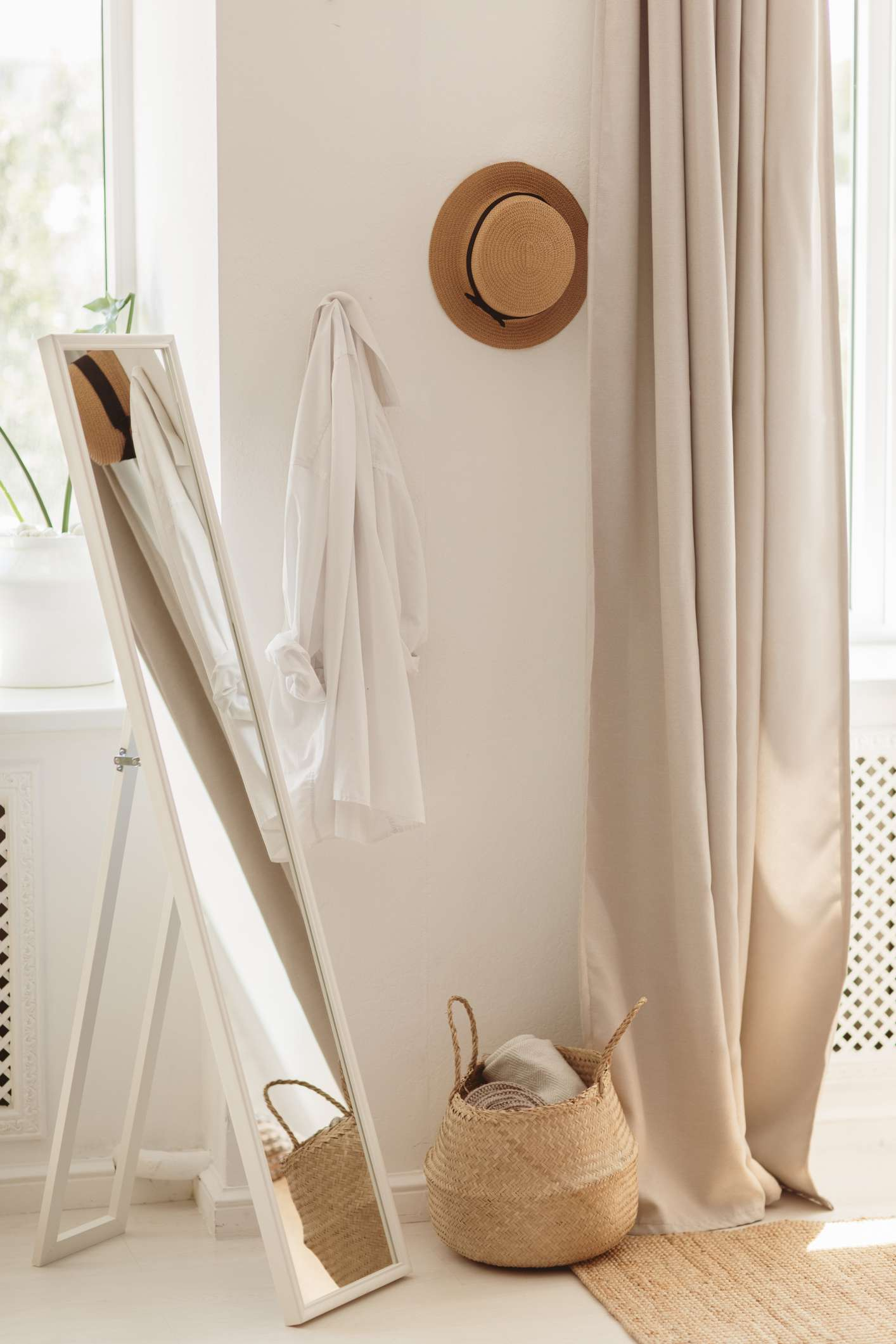 Hallway interior with big white mirror, straw hat, white shirt and basket with clothes near wall. Modern cozy hall interior.