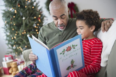 mixed race grandfather reading to grandson at christmas