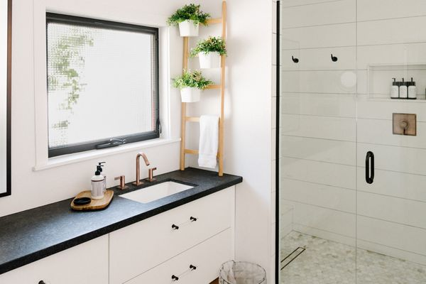 Modern farmhouse bathroom with black countertops and wooden decor items