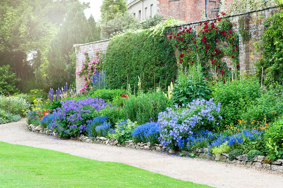 A beautiful summer herbaceous flower border in hazy sunshine