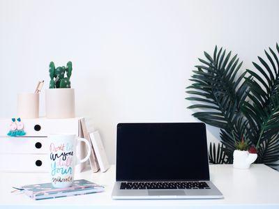 desk with laptop, mug and plants