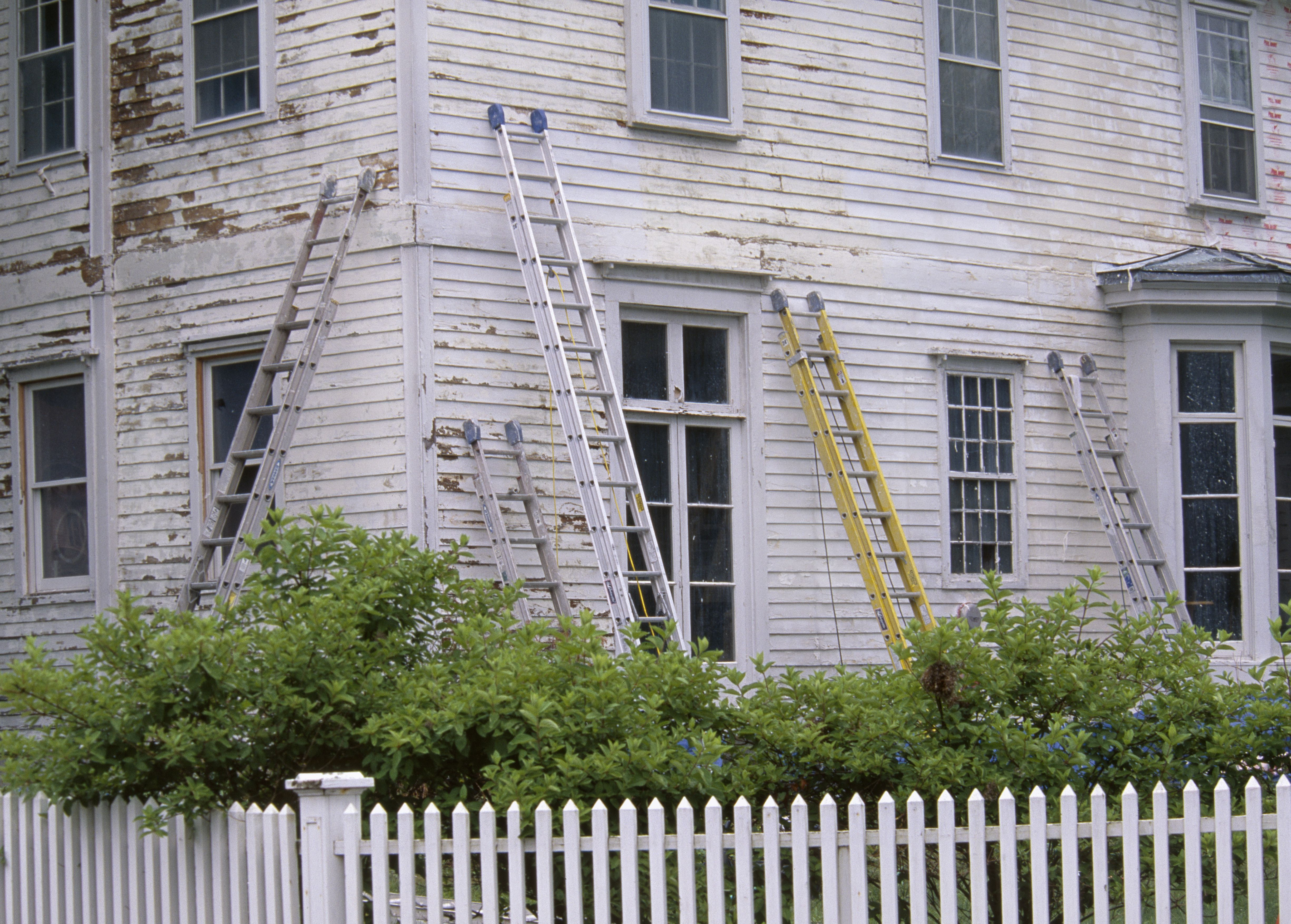 Ladders resting against old house