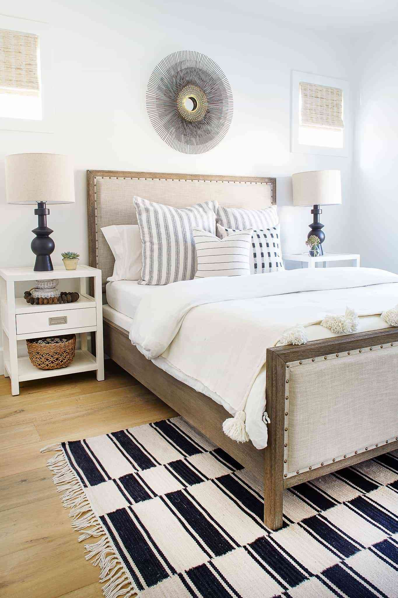 bedroom with white bedding, brown bed frame, white side table, black and white rug under half of the bed