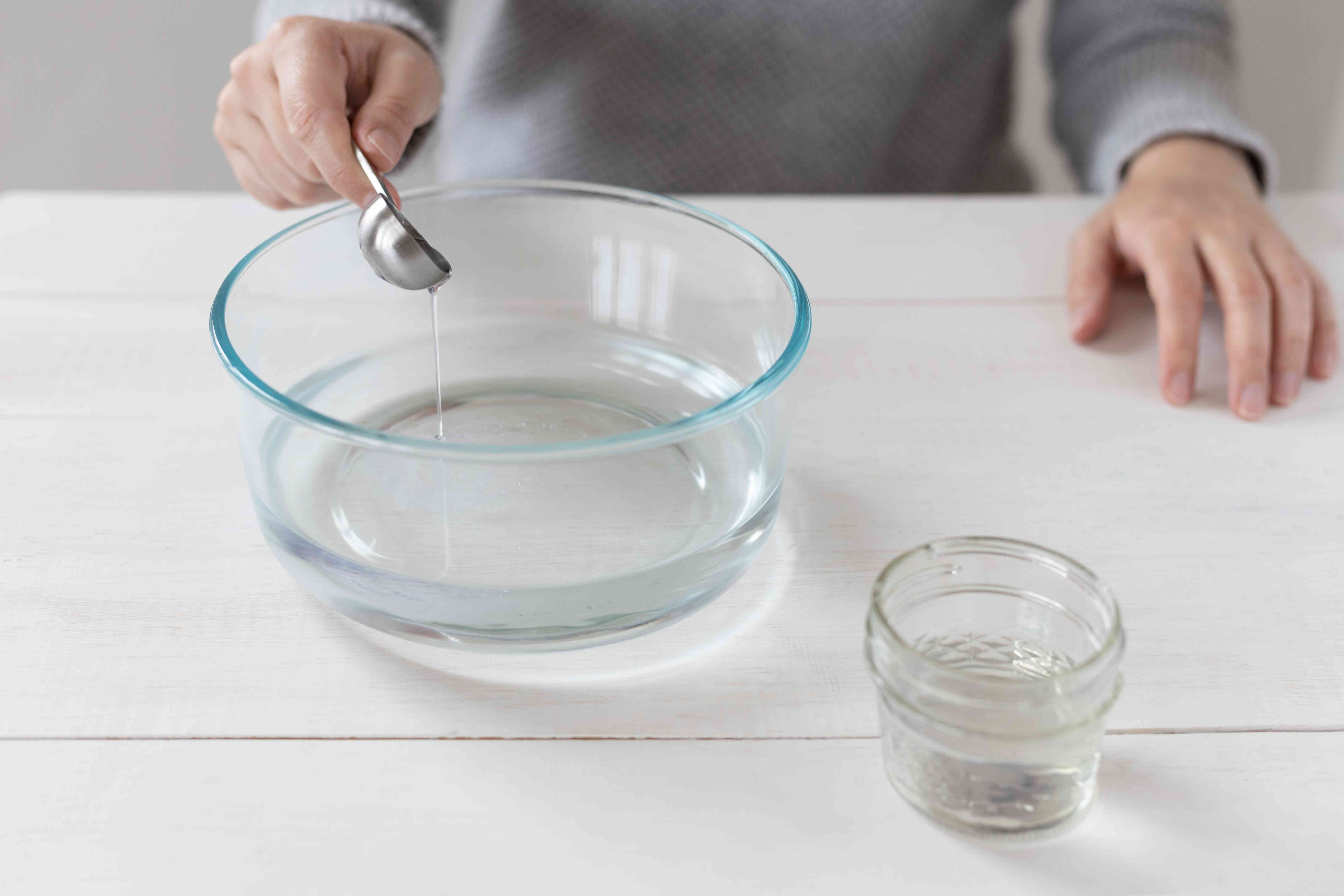 Dishwashing liquid added to glass bowl of water for cleaning mixture