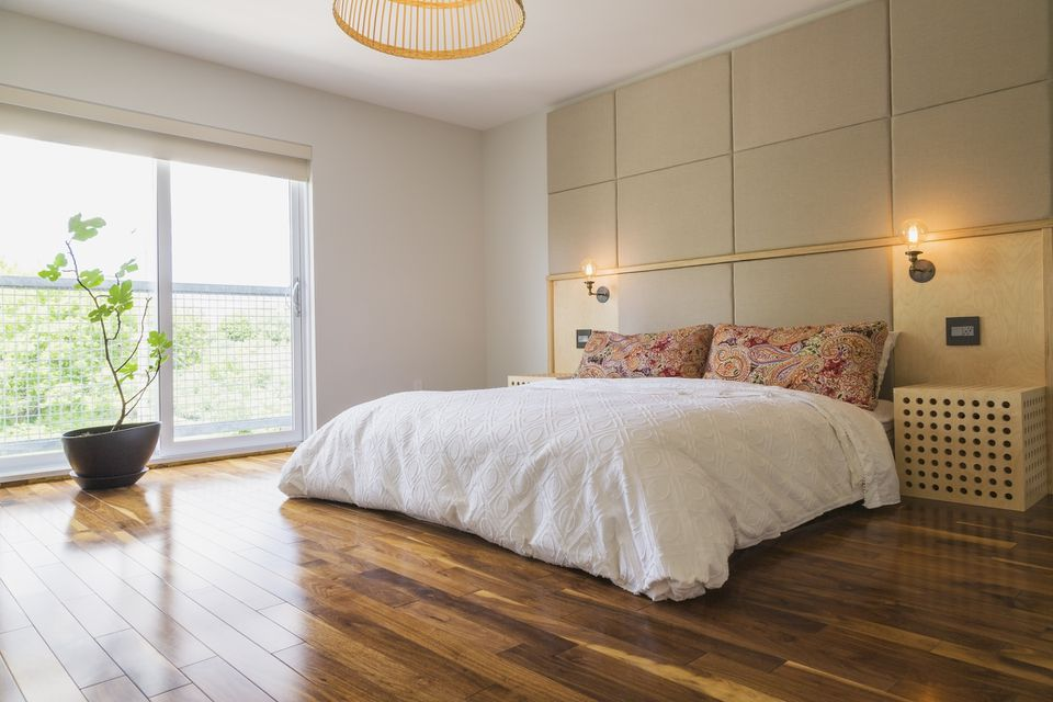 A room with a large bed and wood floors.