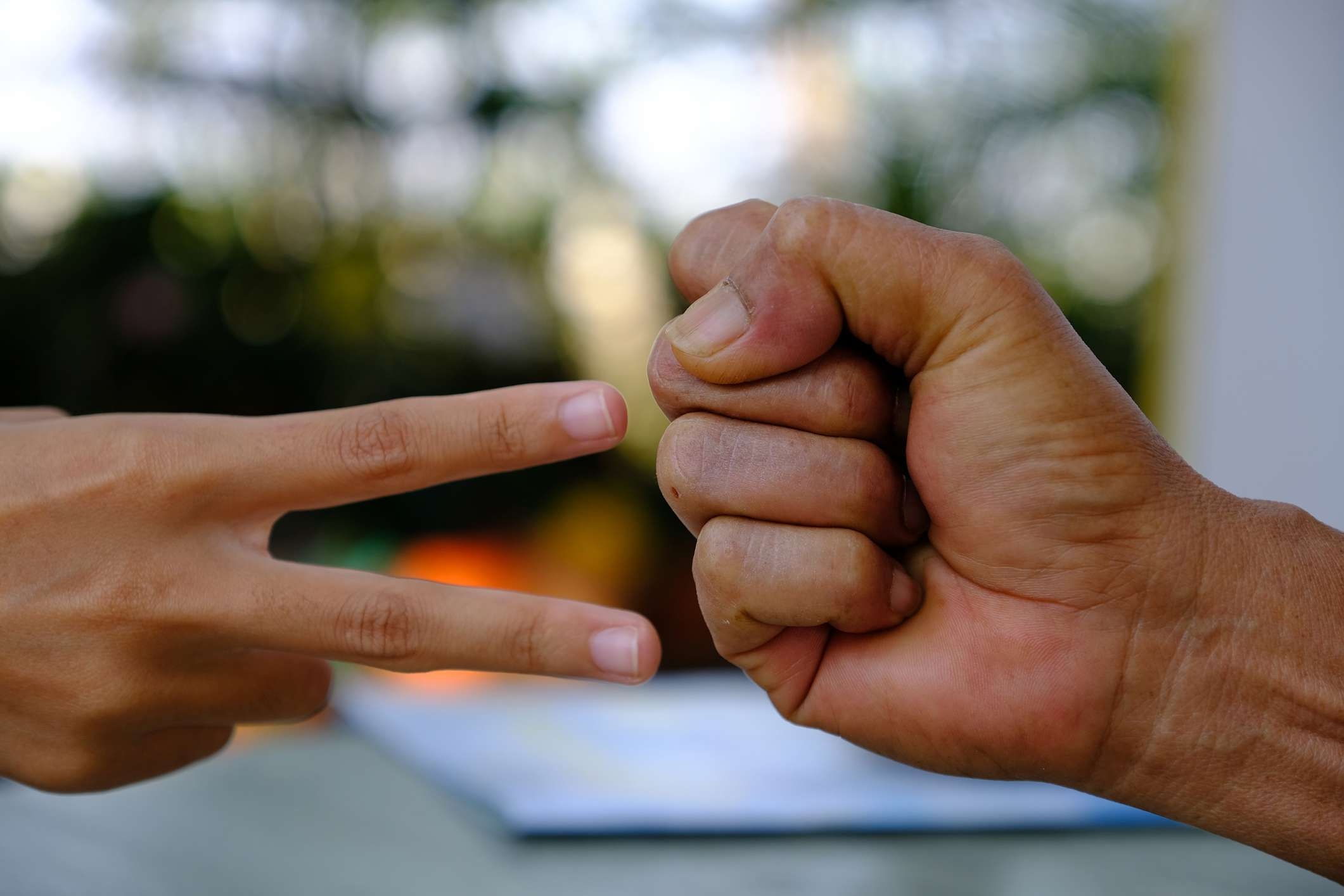 Cropped Image Of People Playing Rock Paper Scissors Outdoors