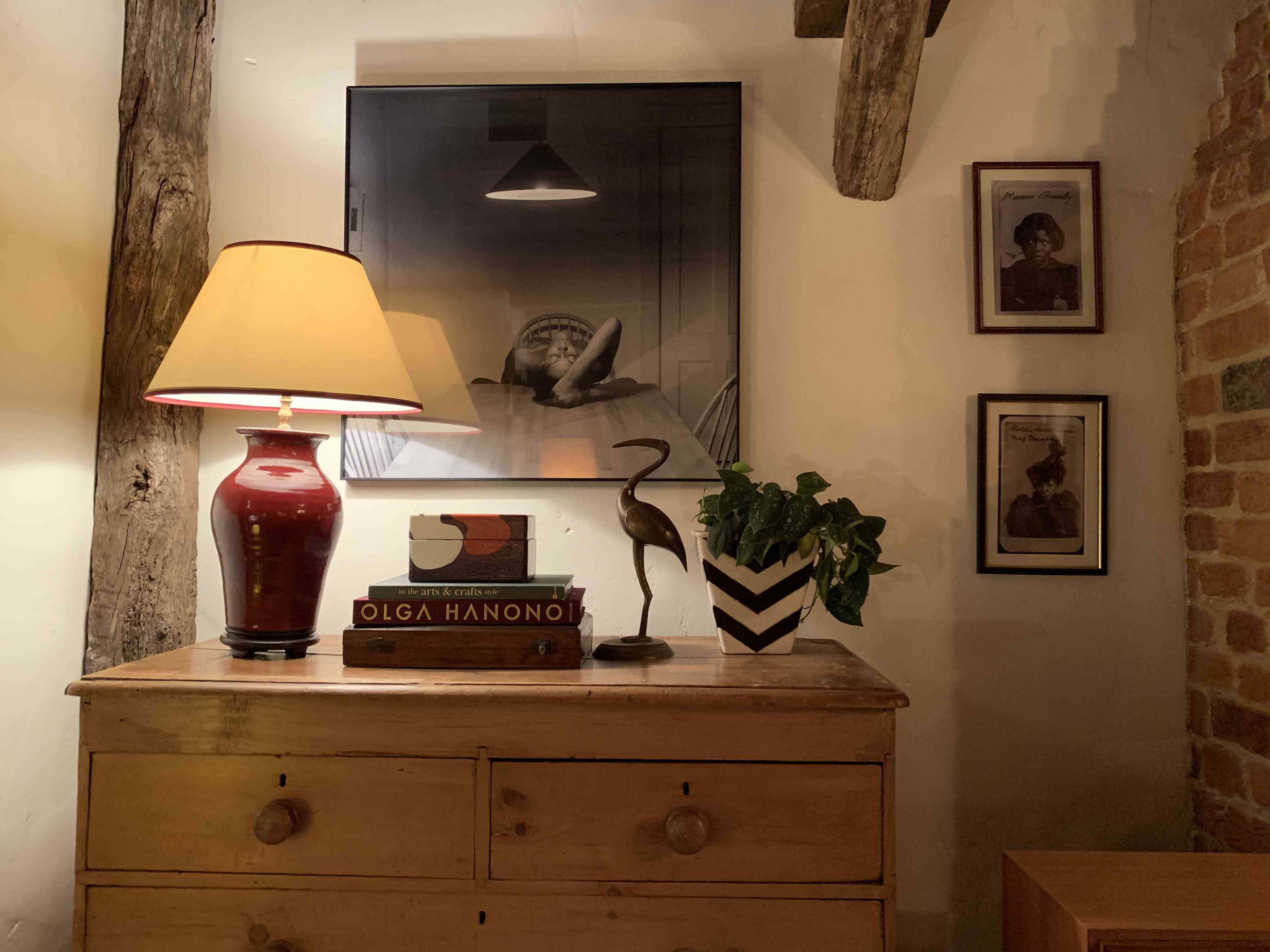 a chest on the set of Master of None features a lamp, books, a statue, art, and exposed wood and beams