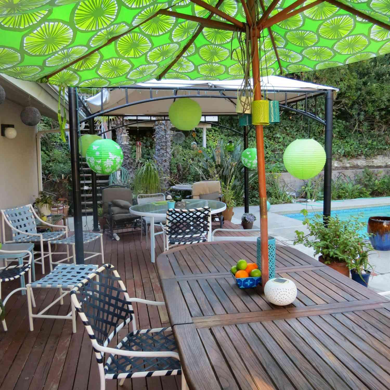 green patio umbrella over wooden table near pool