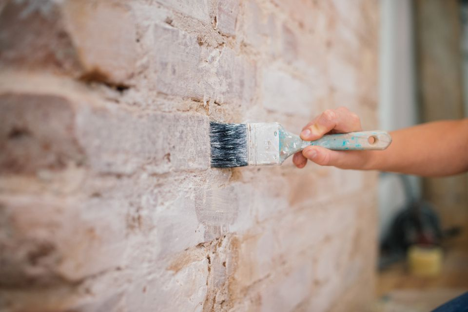 Woman painting brick wall