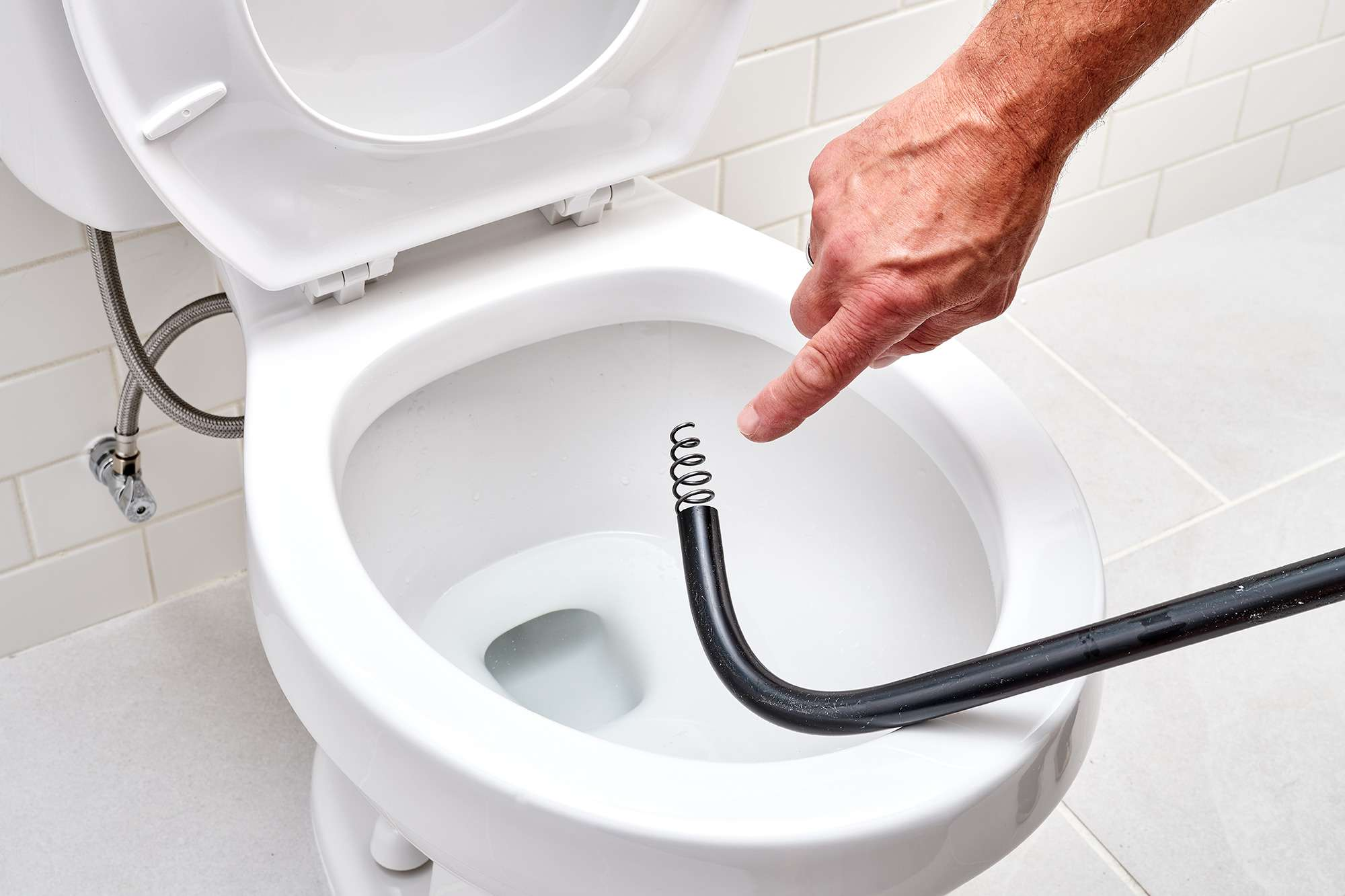 Toilet auger placed on toilet bowl with curled cable showing at end