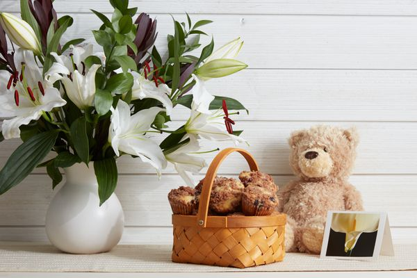 teddy bear, muffins, flowers, and a card