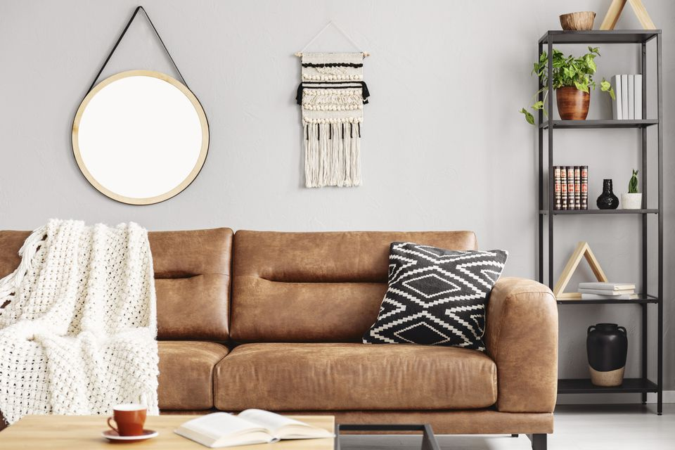 A brown leather couch in a stylish living room.