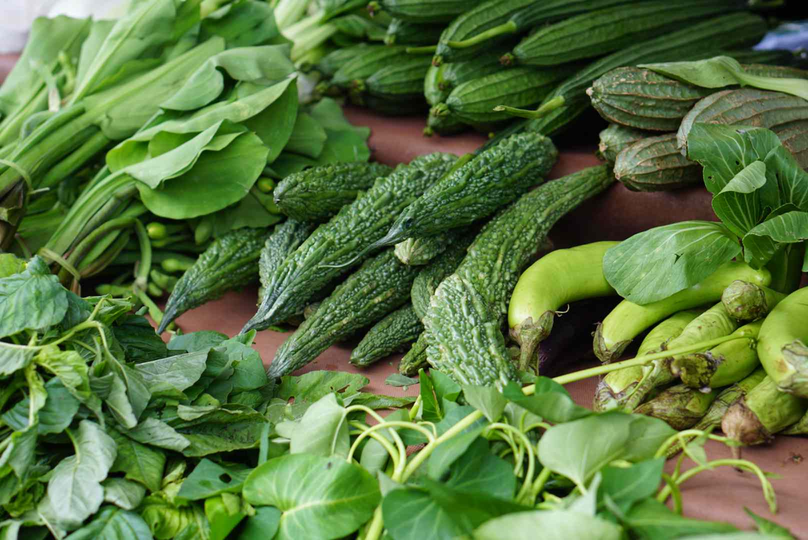 Varieties of green vegetables stacked on a tiered surface