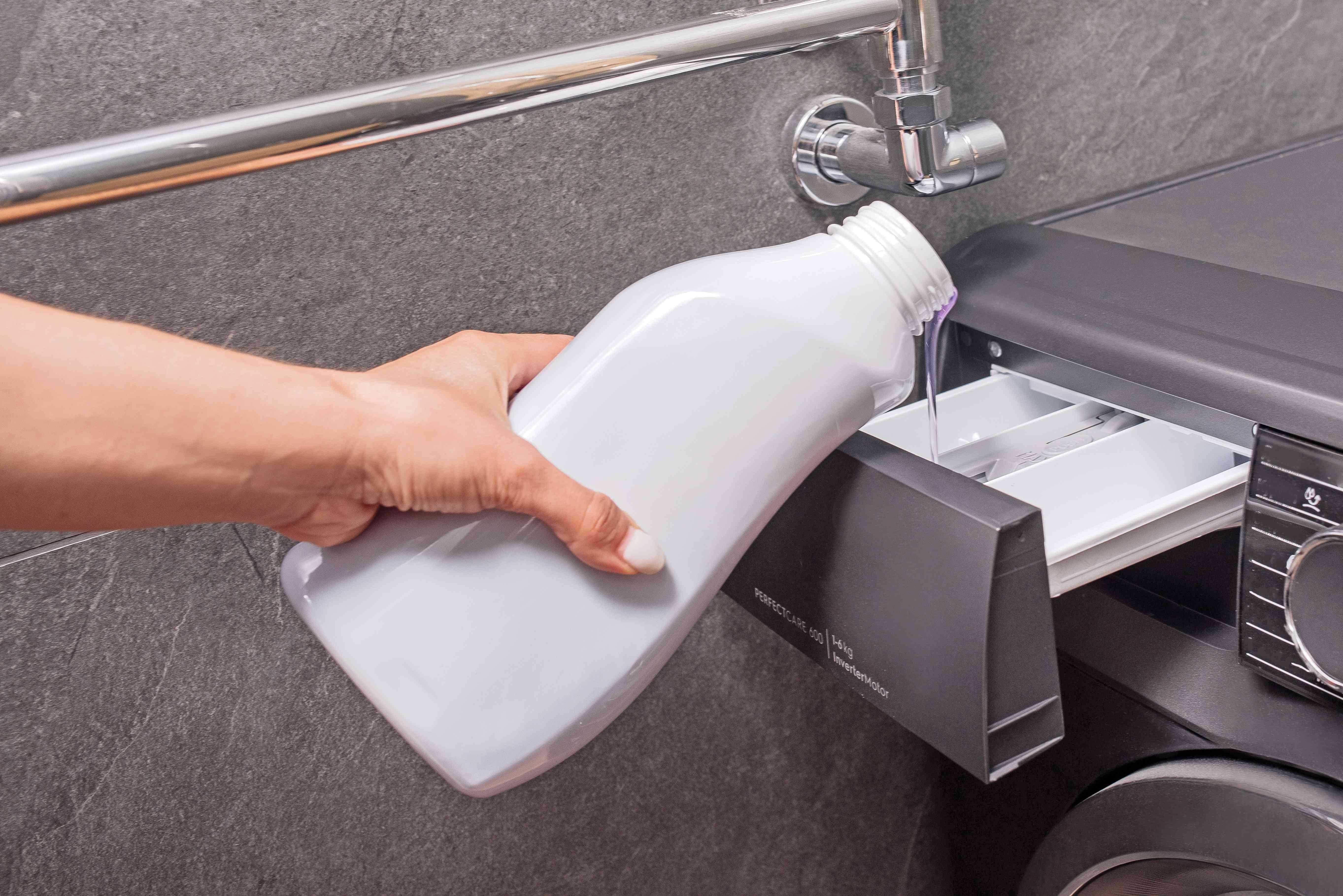 Someone adding chlorine bleach to a washer dispenser