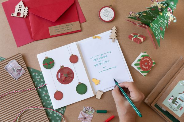 person writing a Christmas card
