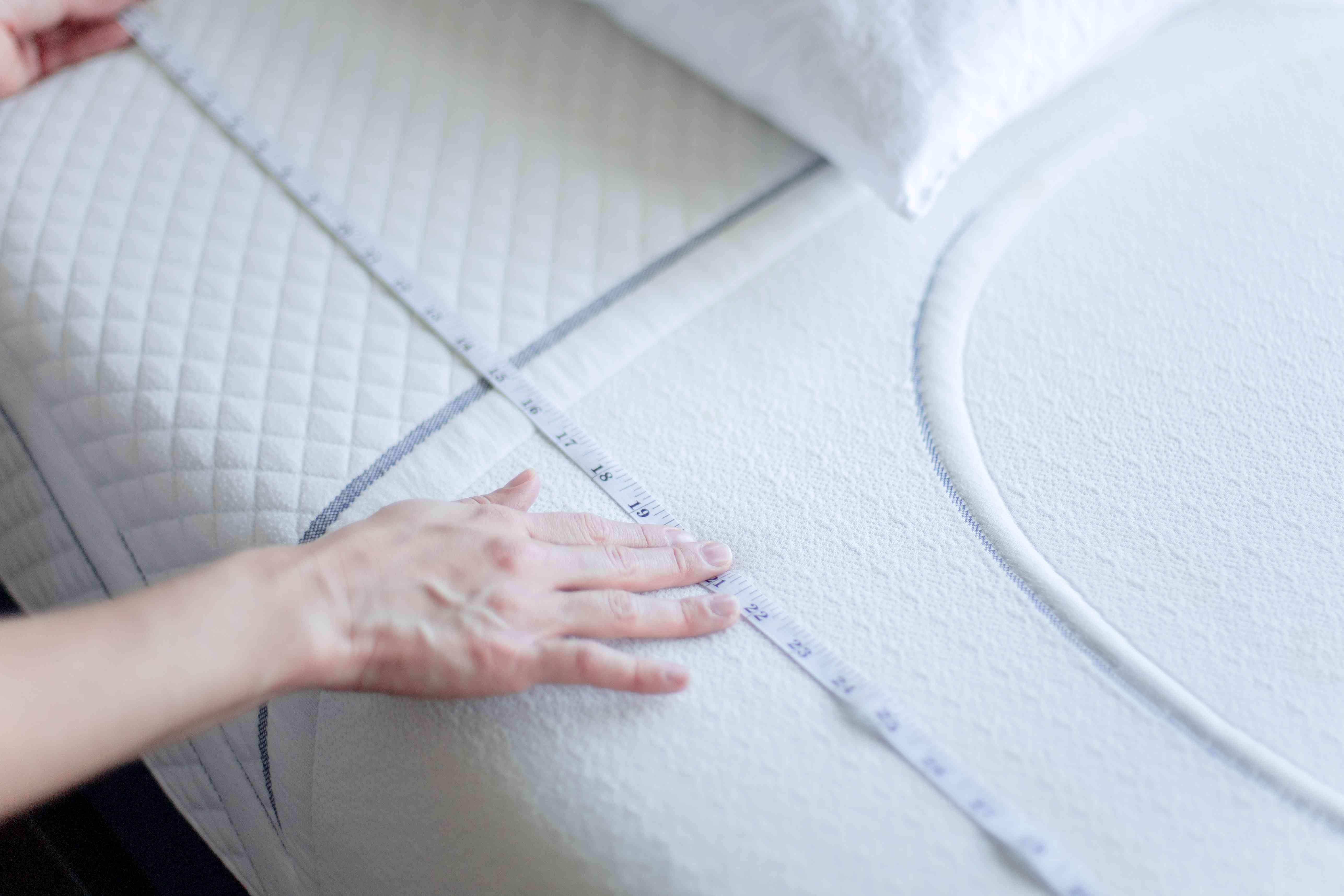 person taking a mattress measurement