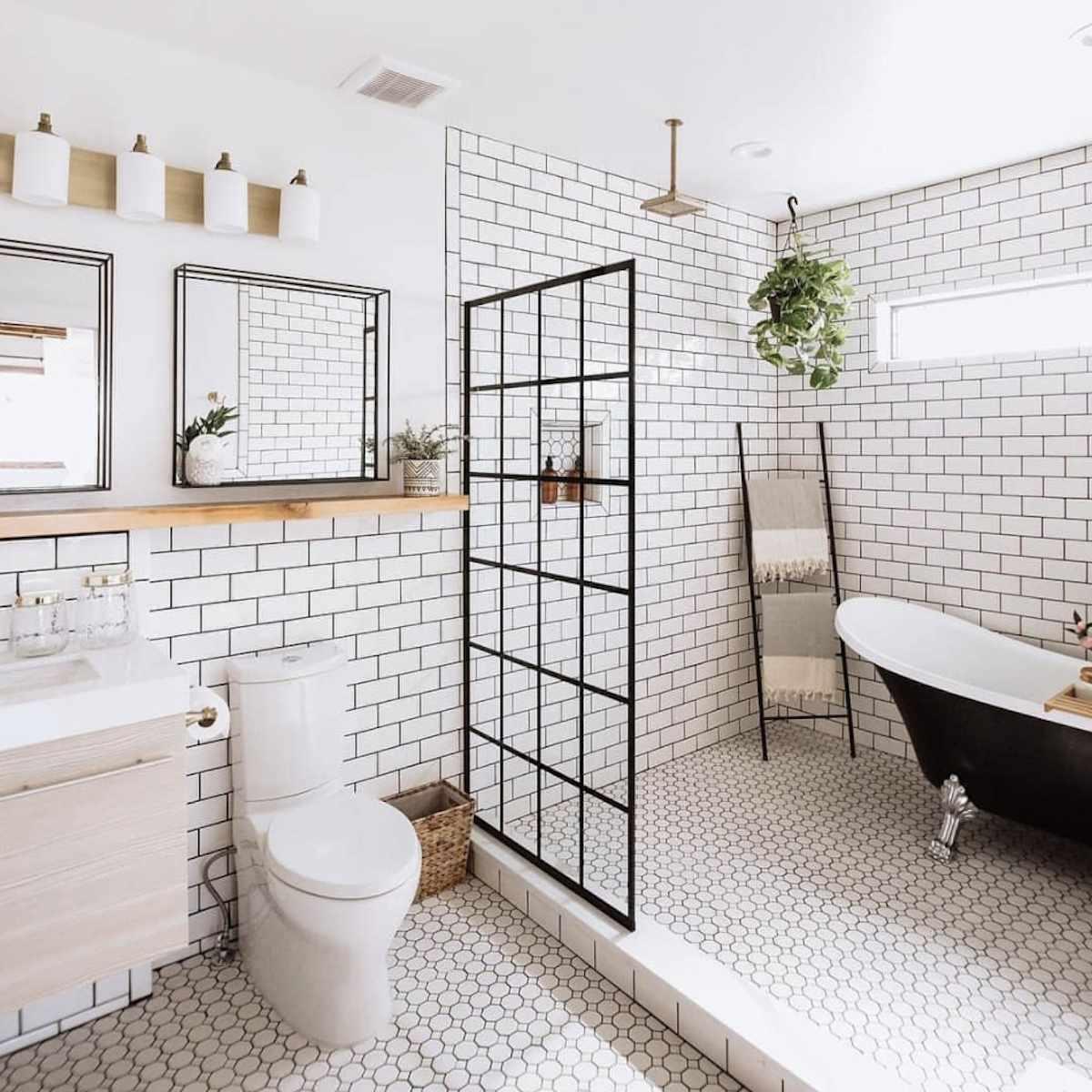 modern subway tile bathroom with black clawfoot bathtub, black ladder holding towels propped up in corner