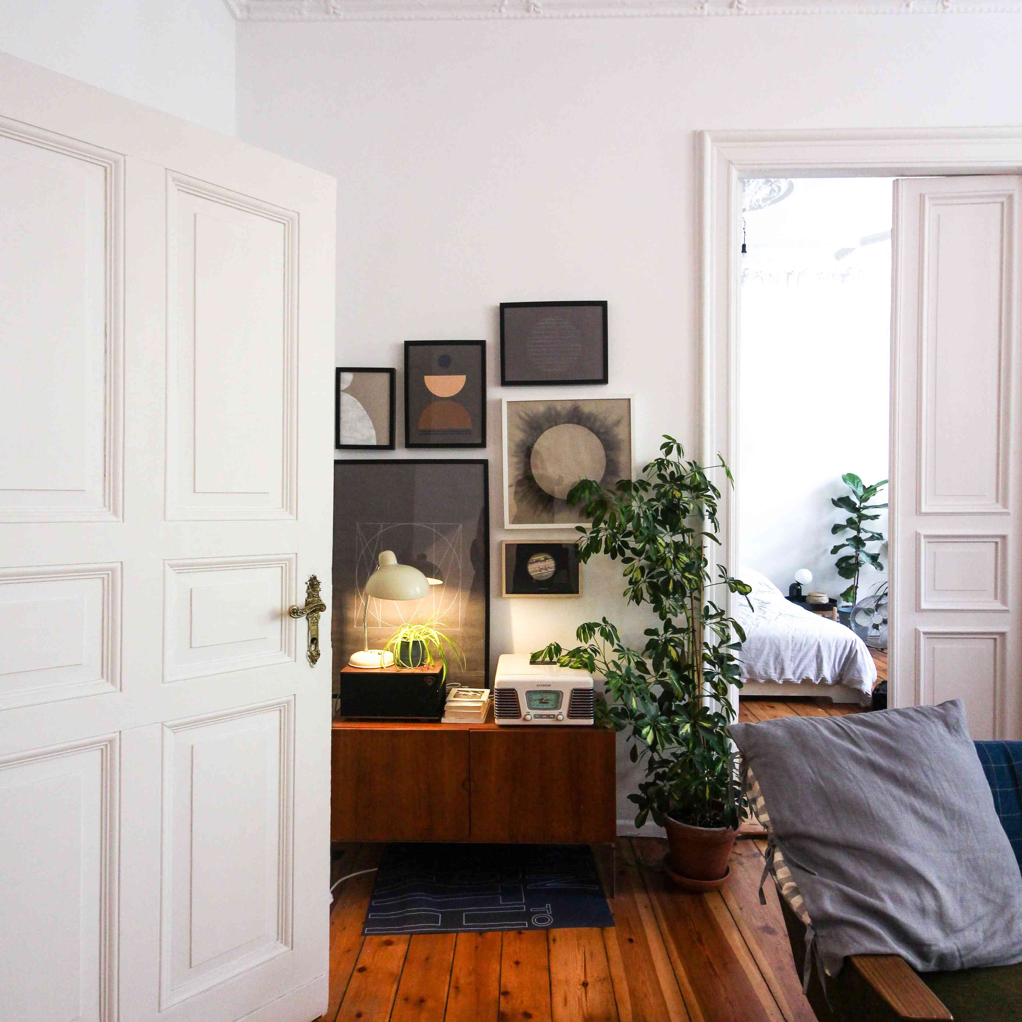 living room with artwork and wood floors facing a bedroom door