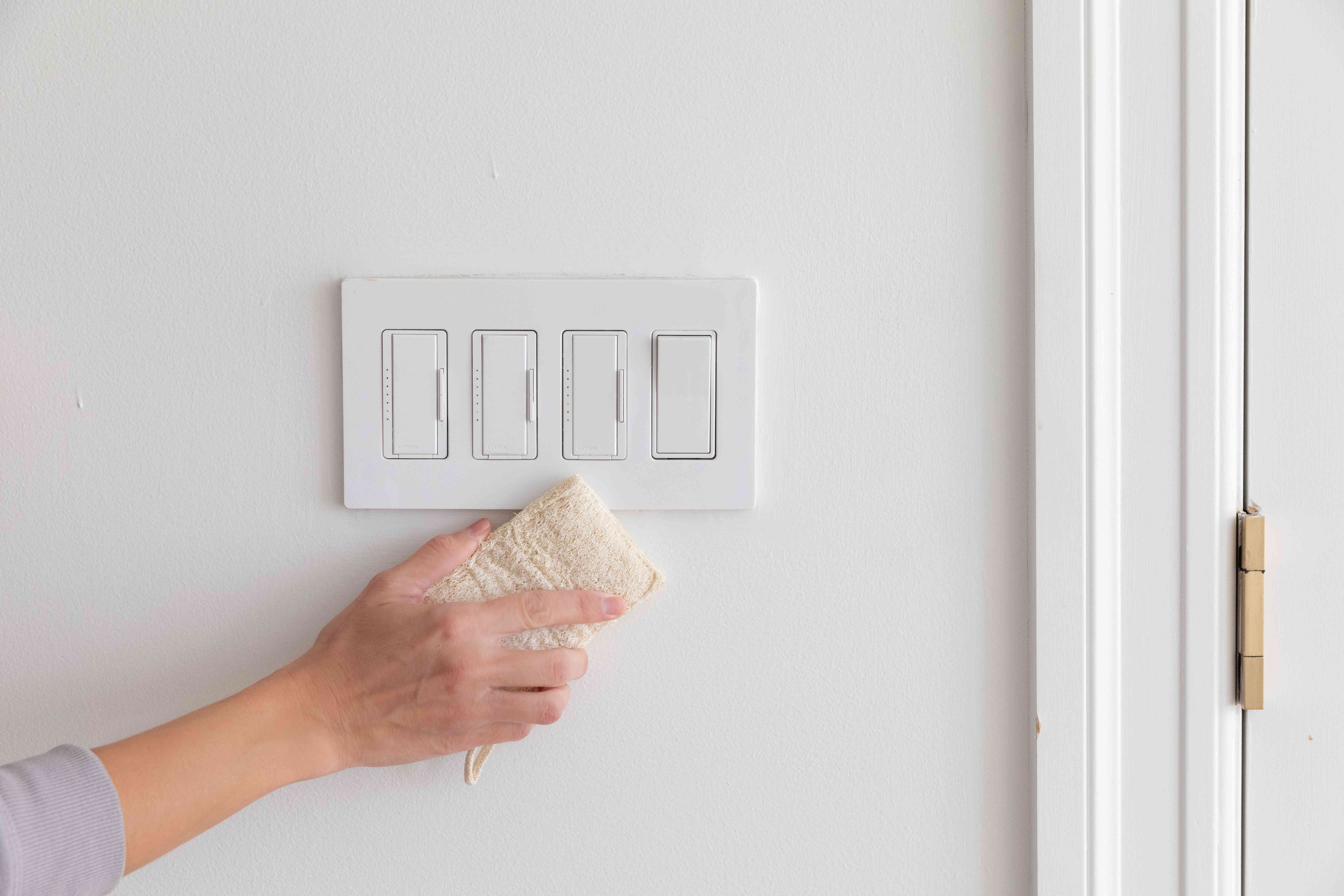 Sponge dipped in baking soda passing over light switch to clean heavy soiled areas