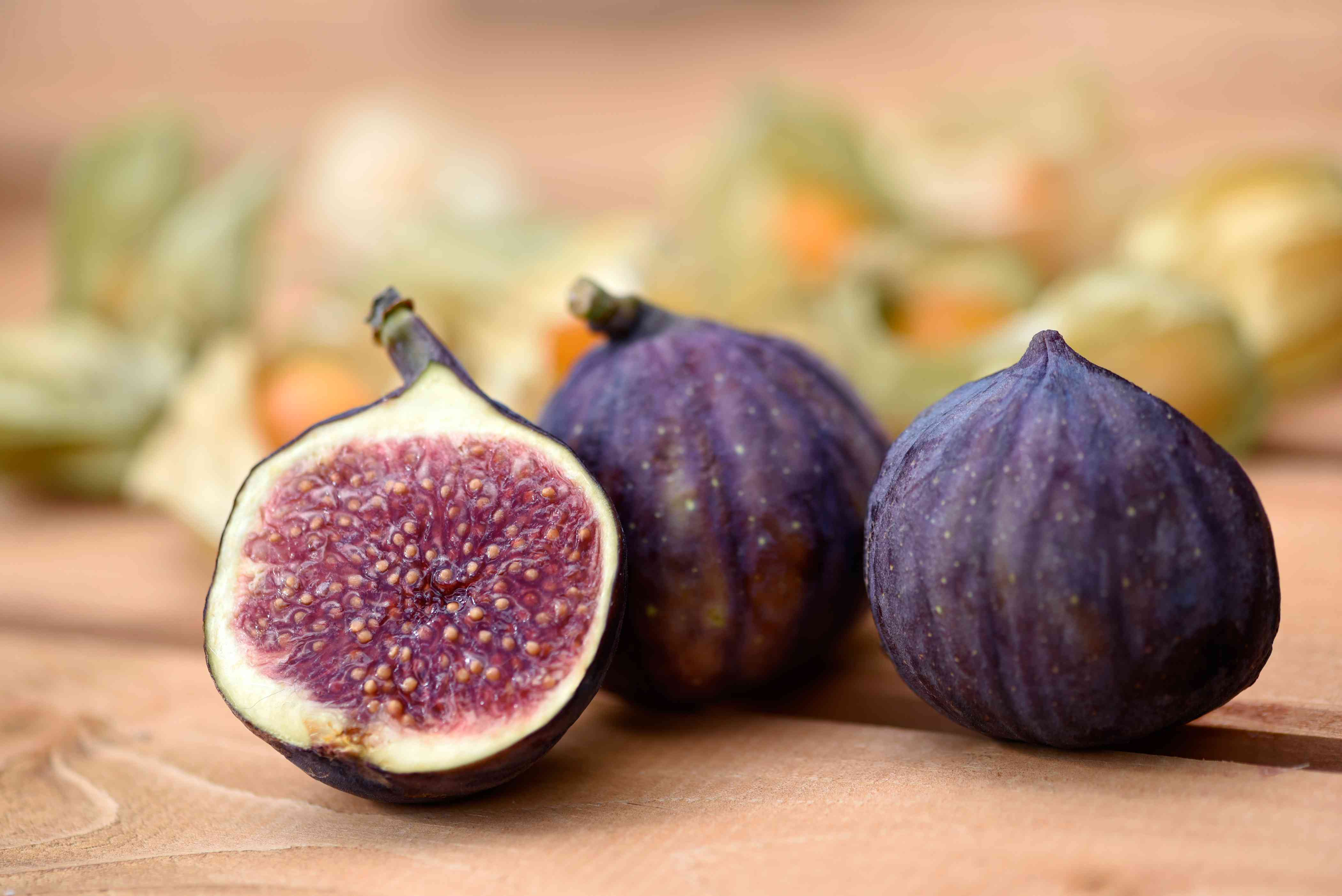 Common fig fruit on wooden surface with one sliced in half