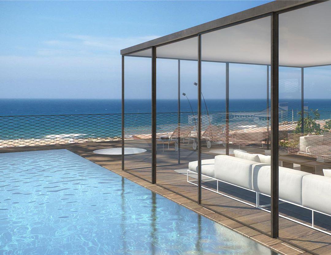 Edificio junto a la playa junto a una piscina