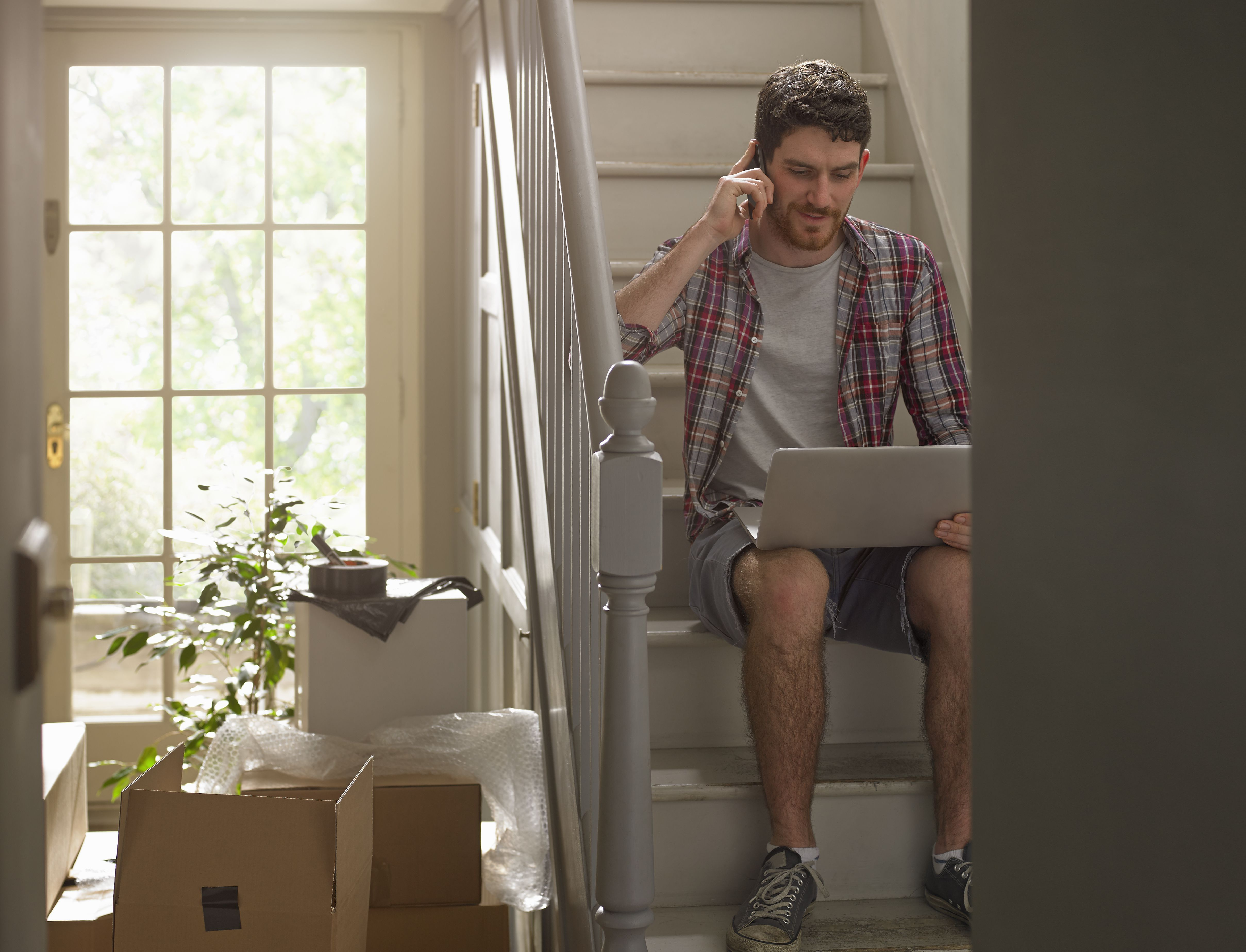 A man moving house working on phone and laptop