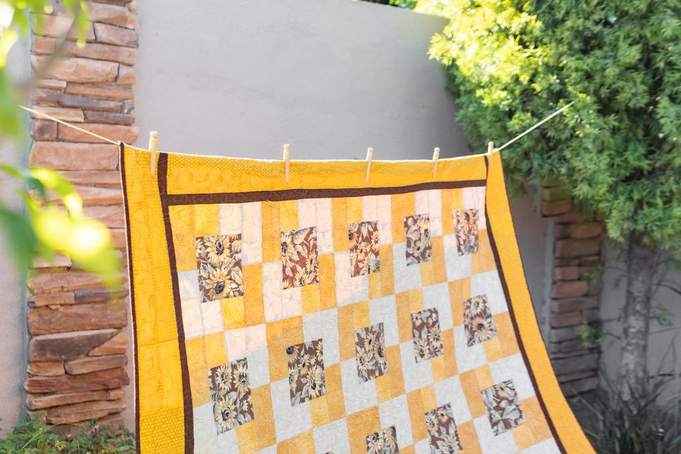 A colorful quilt hanging on a clothesline