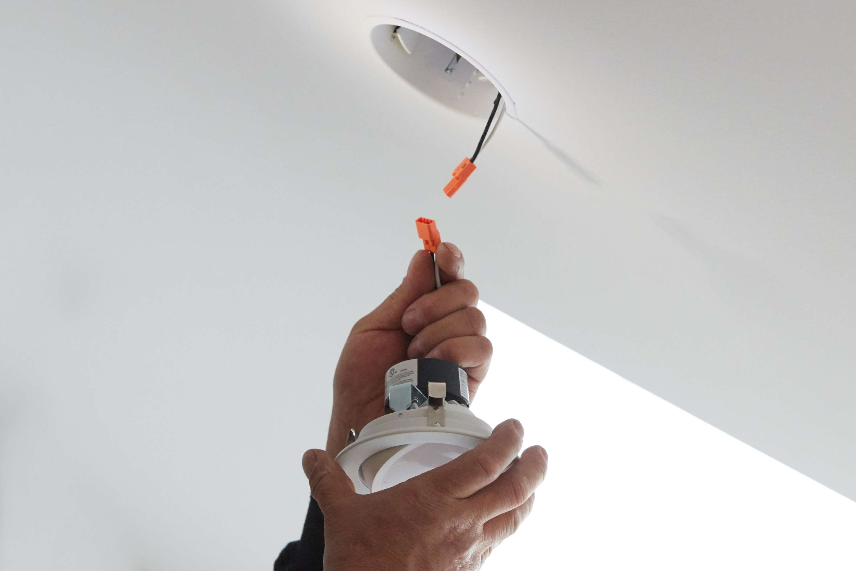 Recessed lighting fixture installed with orange snaps on opposing wires