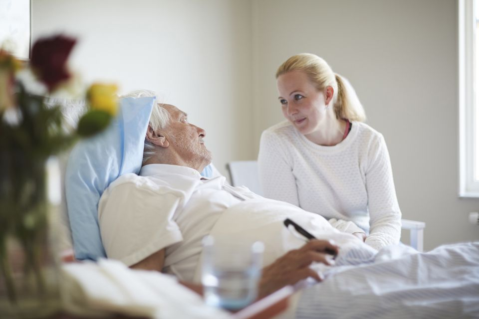 Daughter talking to senior man reclining on hospital bed