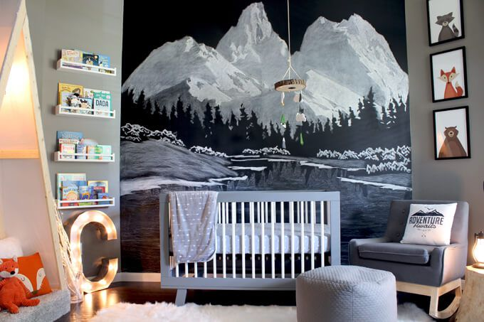 Woodland animal-themed nursery with mountain chalk mural