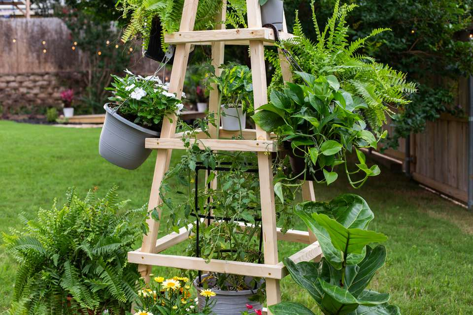 Tall DIY wooden obelisk trellis with planted pots hanging and surrounding fixture