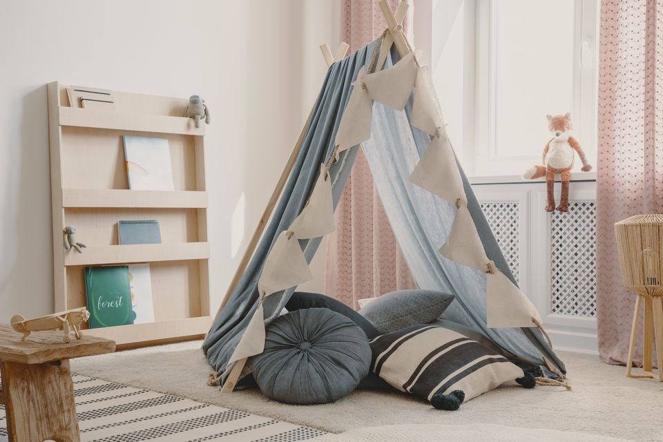 Wooden furniture and tent with pillows in natural scandinavian playroom for kids, real photofox
