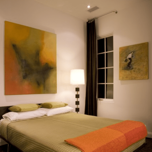 Brown, green, and orange bedroom with artwork on the wall
