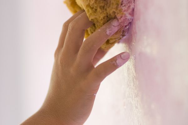 Young woman painting wall with sponge