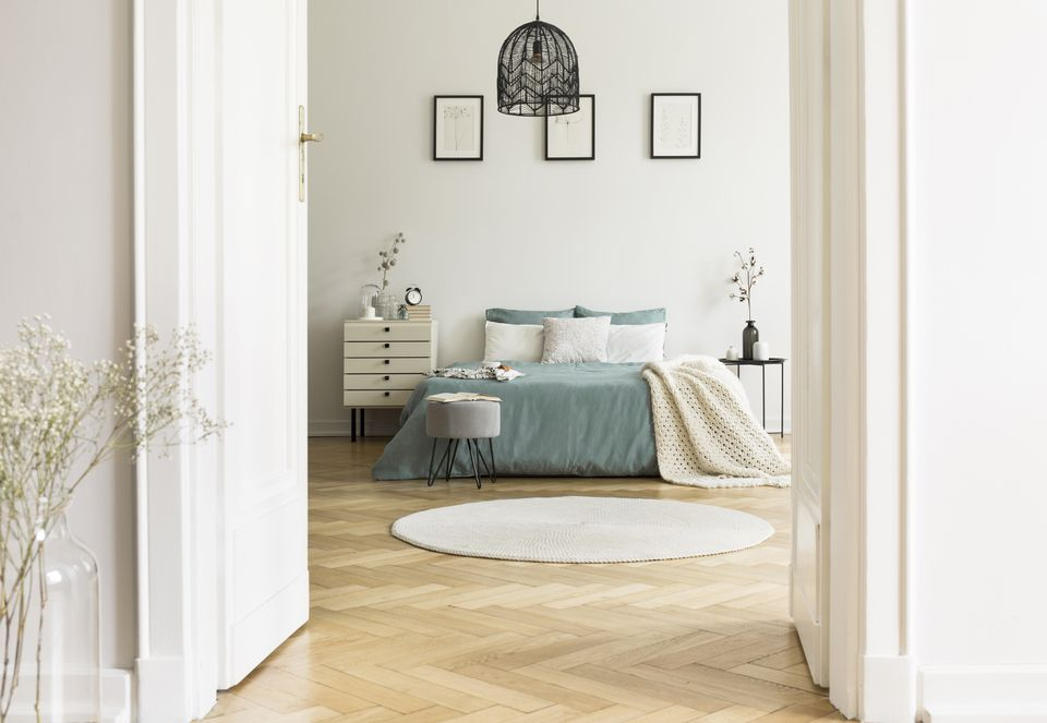 Real photo of white bedroom interior with round rug, king-size bed with pillows and pastel sheets, simple posters and herringbone parquet