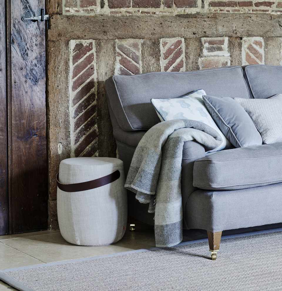 a cozy throw sits on an upholstered sofa