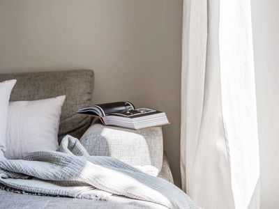 Image of a couch with pillows, blanket, and an open book on the edge. The couch is next to a white curtain