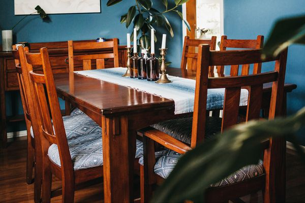 Quality wood dining table with patterned seating and candles in the center