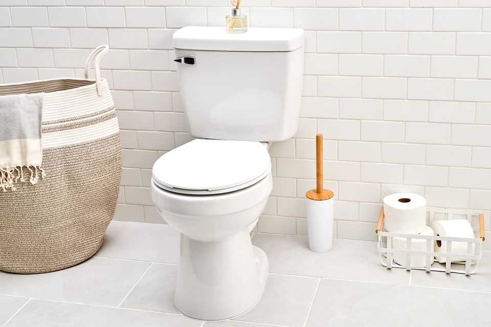 Replacement toilet inside white walled and tiled bathroom with light decor