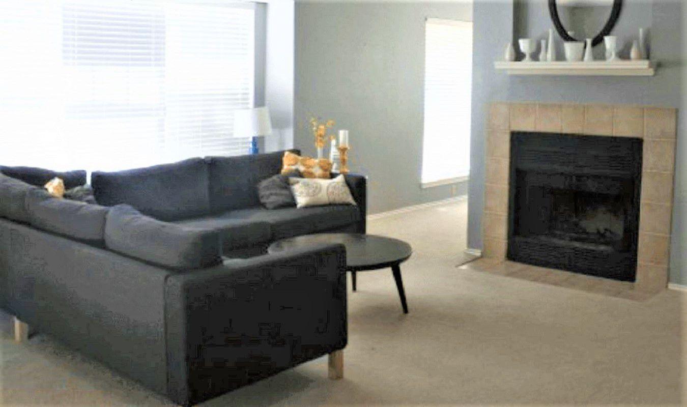 Sala de estar simple y paredes grises con chimenea y sección gris antes del cambio de imagen