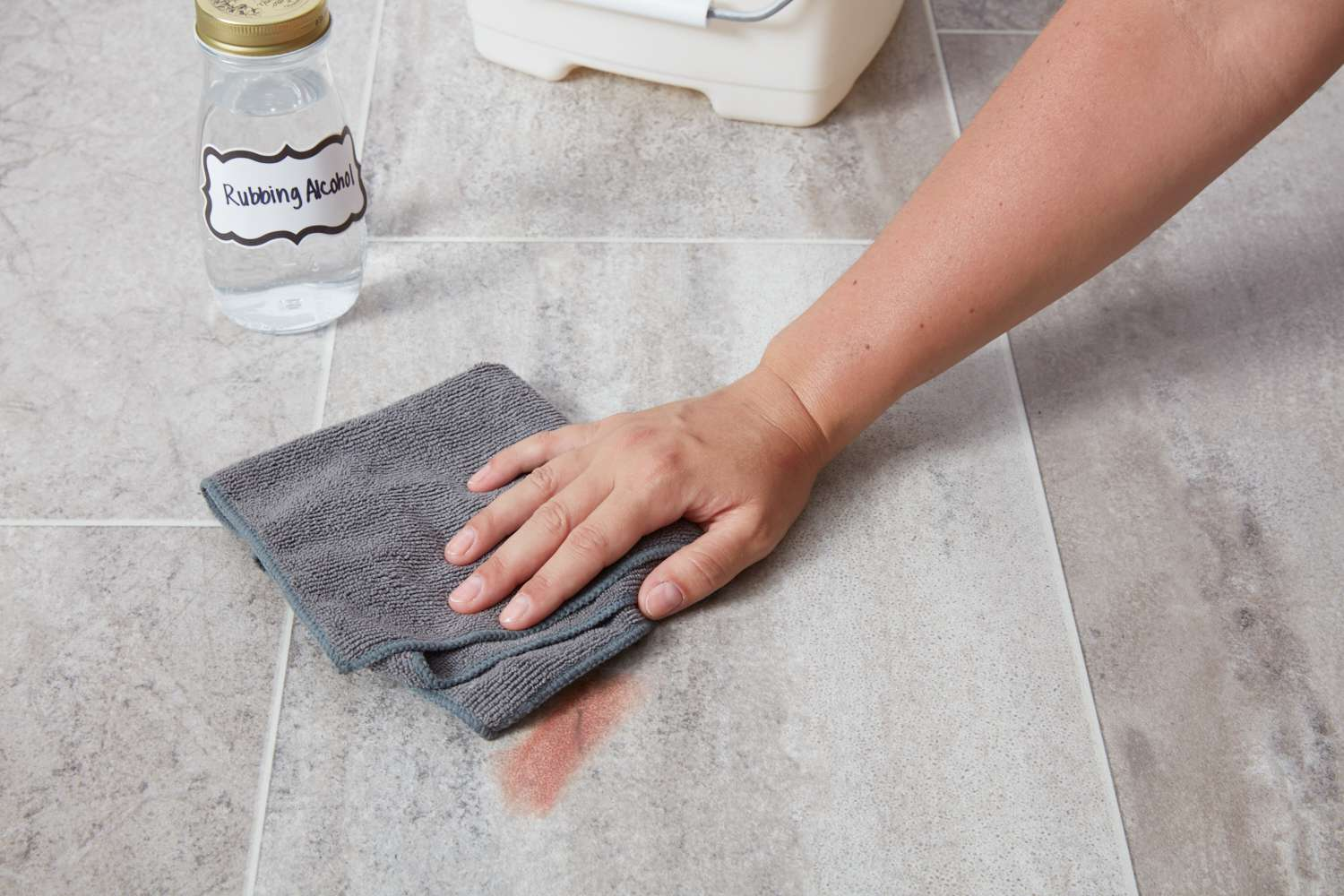 Scrubbing vinyl floor stain with rubbing alcohol and microfiber towel