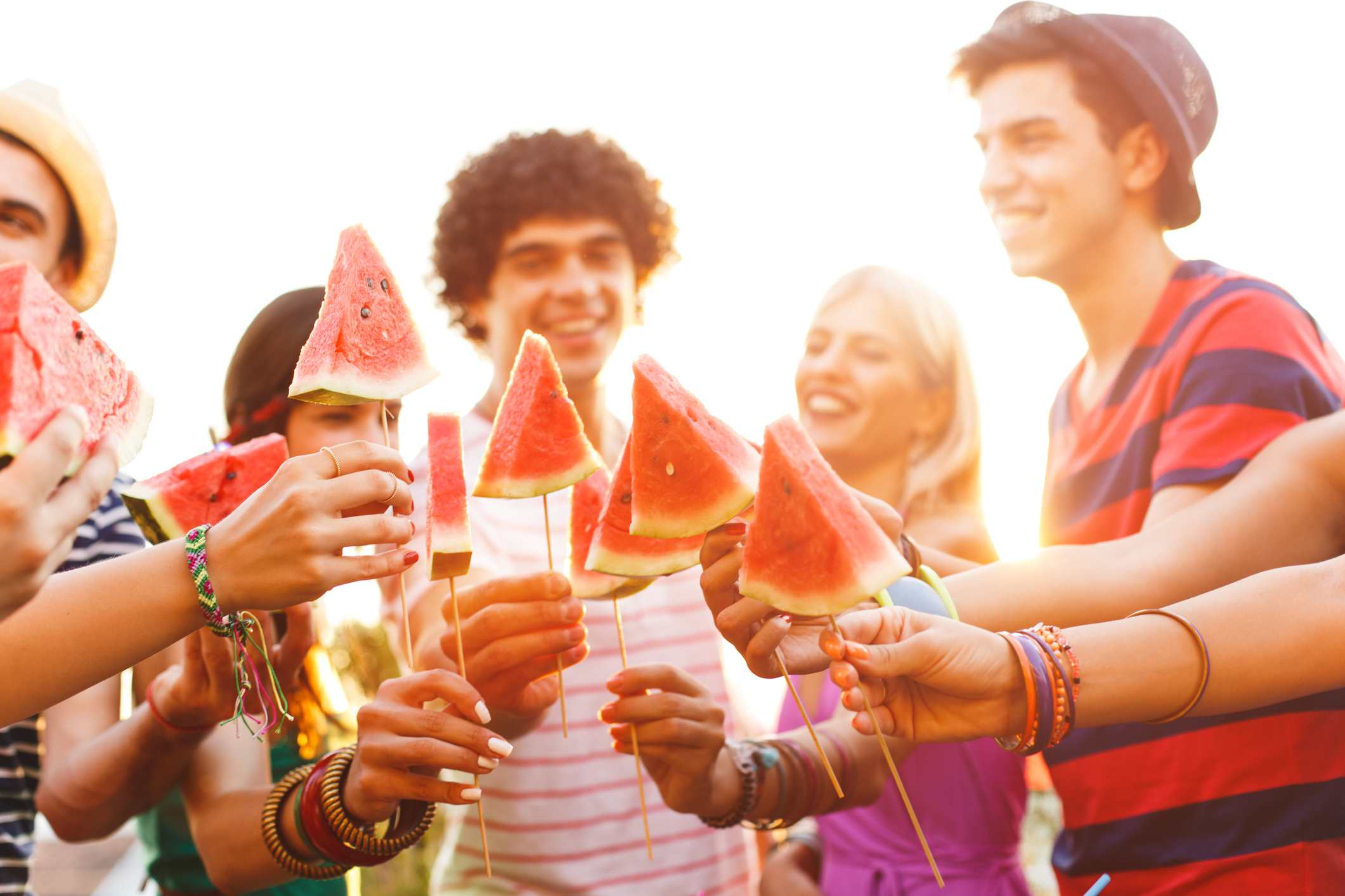 Group of people holding slices of watermelon on sticks.