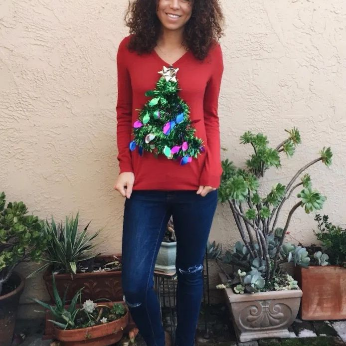 A woman wearing a red ugly Christmas sweater