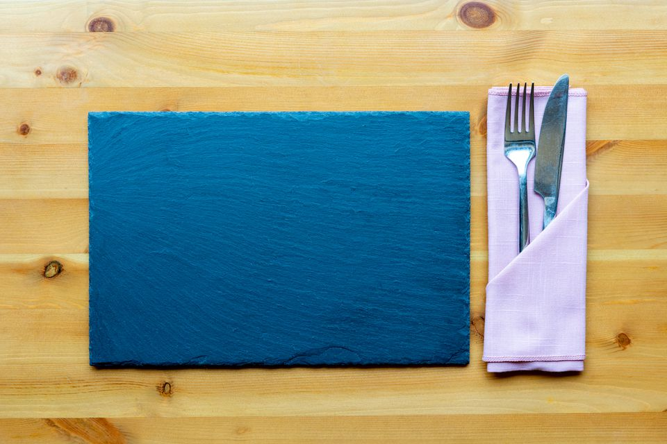 Place mat and folded napkin with silverware on wooden table